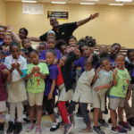 A group of black children in Elementary school cheering after NBT event